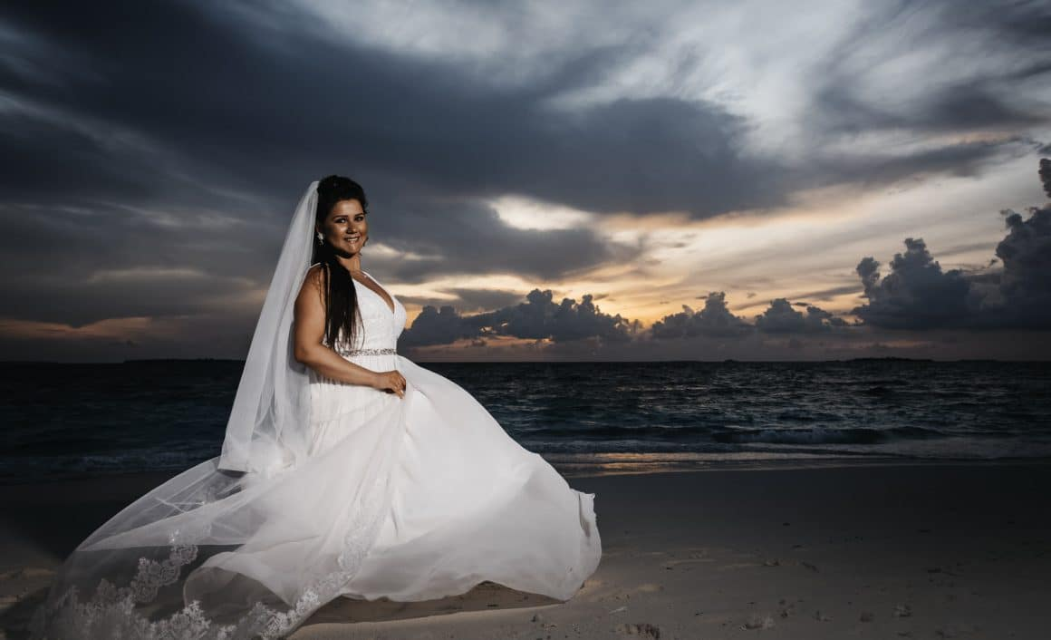 photography of bride sitting on the beach for maldives sunset